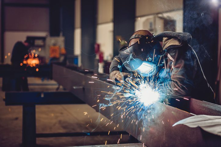 Man welding metal, order from a phone system for manufacturers.